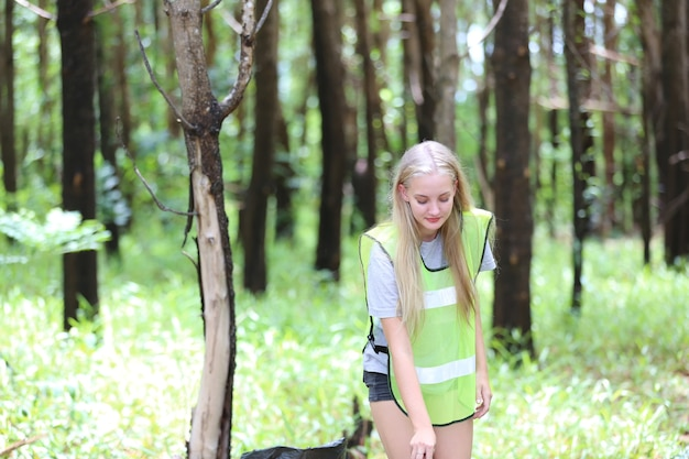 녹색 자원 봉사. 쓰레기 봉투를 들고 공원에서 쓰레기 수거를 돕는 낙관적인 두 자원봉사자들은 쓰레기를 주워서 검은 쓰레기 봉투에 넣고 있습니다. 생태 보호 개념입니다.
