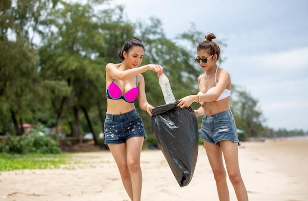 グリーンボランティア。ゴミ袋を持って公園でゴミ拾いを手伝う楽観的な2人のボランティアがゴミ袋を拾い上げて黒いゴミ袋に入れています。エコロジー保護の概念。