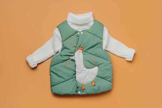 주황색 바탕에 따뜻한 스웨터가 있는 녹색 조끼. 스타일리시한 아동복. 겨울 패션 복장