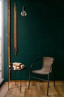 Зеленая стена с плетеным стулом и журнальным столиком. на столе книги, зефир, чашка и цветок. фото высокого качества
