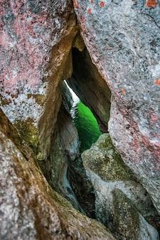 Зеленая вода видна через узкую щель в гранитной скале