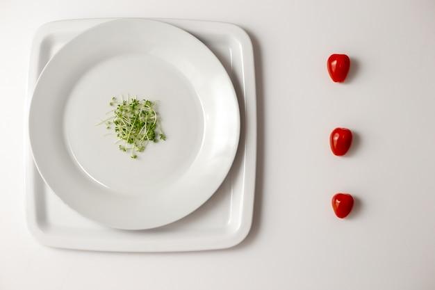 丸い白いプレートと行に新鮮な3つの赤いチェリートマトの側面に緑のクレソン