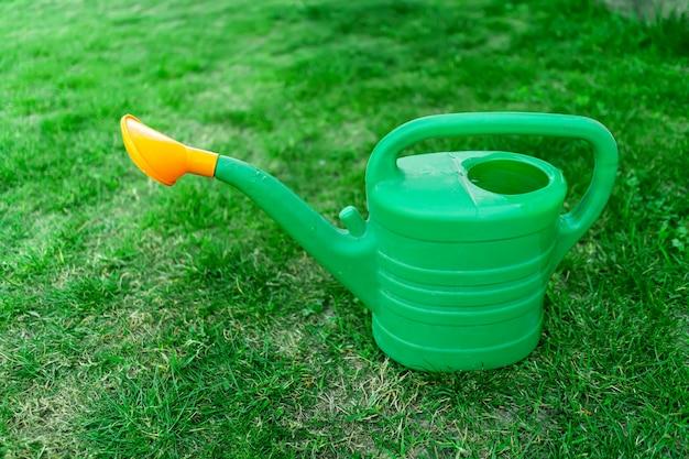 Зеленая лейка на лужайке