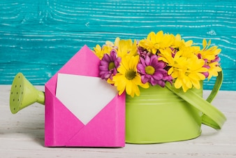 Green watering can with flowers and pink envelope