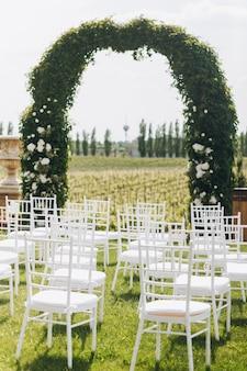 緑の結婚式のアーチと白い椅子