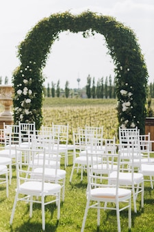 Green wedding ceremony archway and white chairs