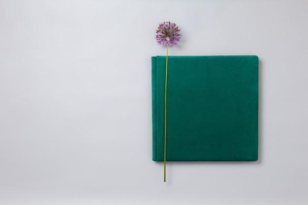 テキストの美しい写真集のクローズアップのためのコピースペースと灰色の背景に緑の結婚式のフォトアルバム