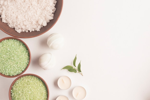 Green and white herbal sea salt with spa bomb and candles on white background