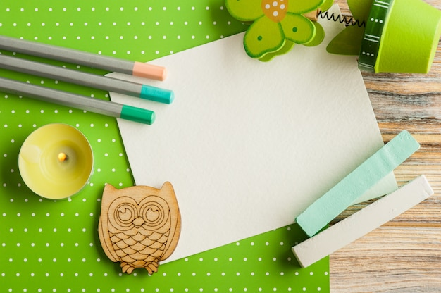 Green white polka dot desk with set of colorful pencils