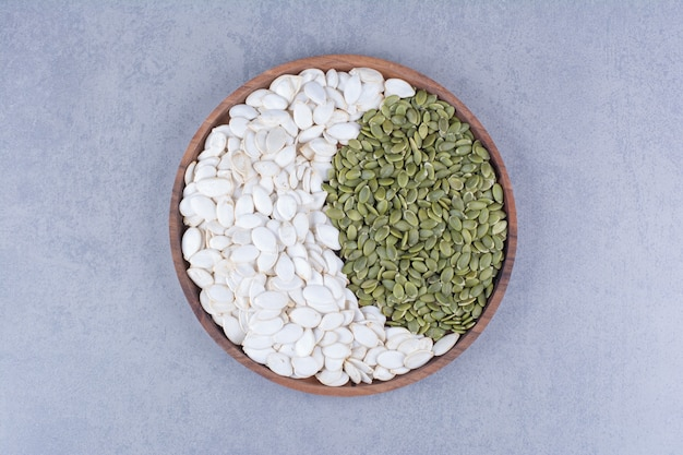Green and white pumpkin seeds on wooden plate on marble.