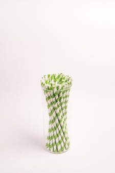 Green and white striped drinking tubes in a glass isolated on a light-colored background