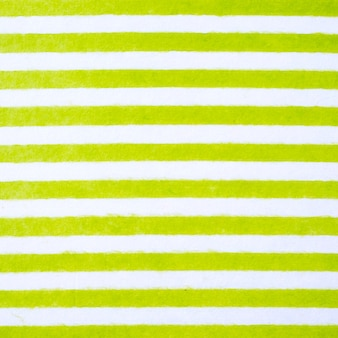 Green and white striped pattern on mulberry paper textured background, detail close-up