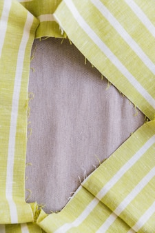 Green and white stripes fabric material forming frame on plain sack cloth