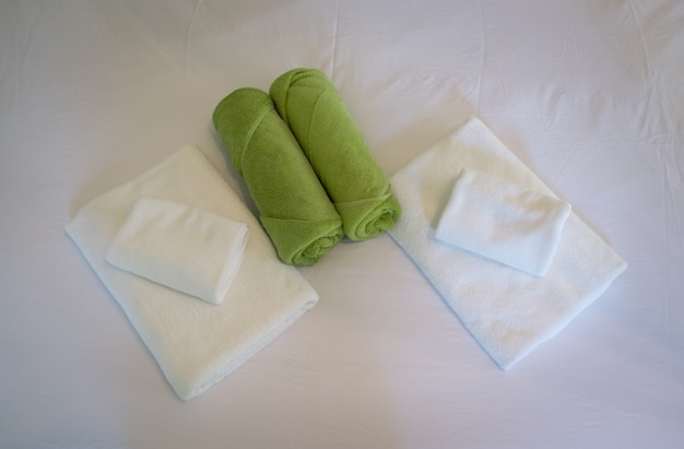 Green and white towels on bed in bedroom