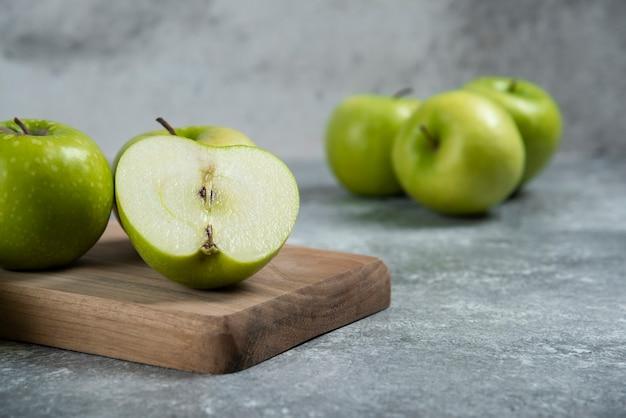녹색 전체 및 얇게 썬 사과 나무 보드에.