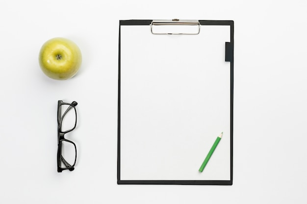 Green whole apple with eyeglasses and green pencil on white clipboard over white office desk