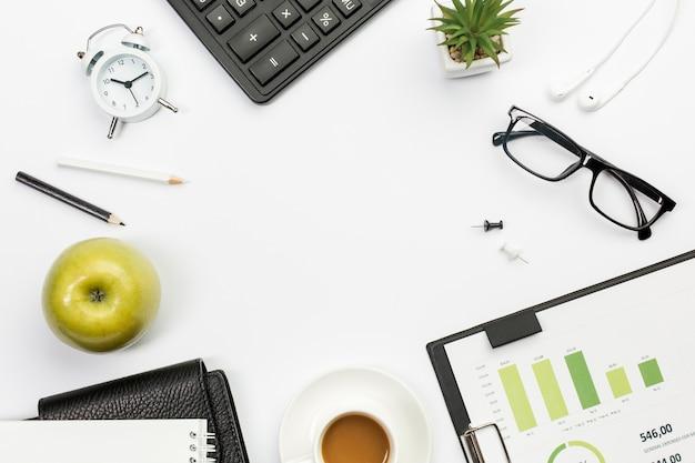 Зеленое целое яблоко с канцелярскими принадлежностями на белом офисном столе