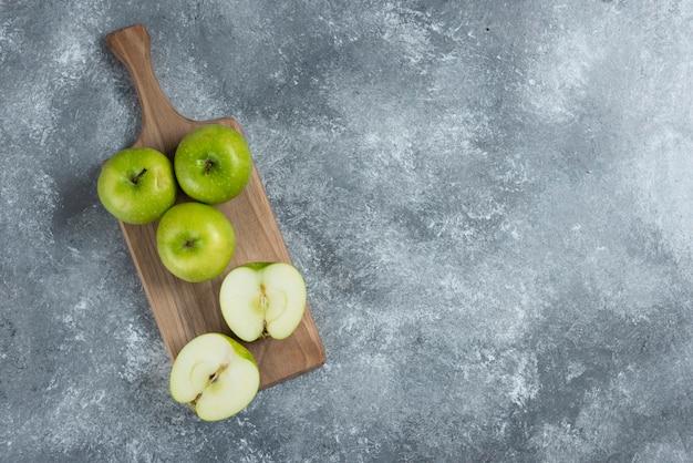 Mele intere ed affettate verdi sulla tavola di legno.