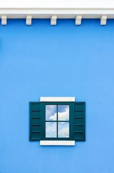 푸른 벽에 있는 거울에 하늘 여름과 흰 구름을 반영하기 위해 열린 녹색 창 집, 배경을 위한 이탈리아 고전적인 빈티지 스타일 복사 공간의 오래된 나무 창틀