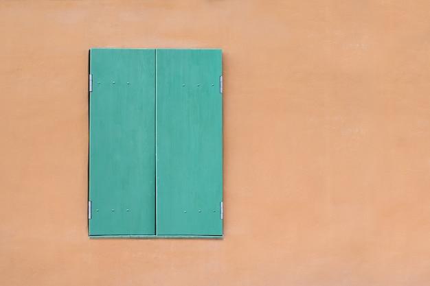 Зеленое окно на желтом фоне. окно с закрытыми ставнями. шаблон. фон. макет