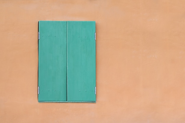 Green window on yellow background. window with closed shutters. template. backdrop. mockup