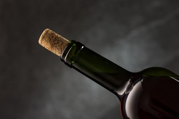 Green wine bottle with cork on dark background