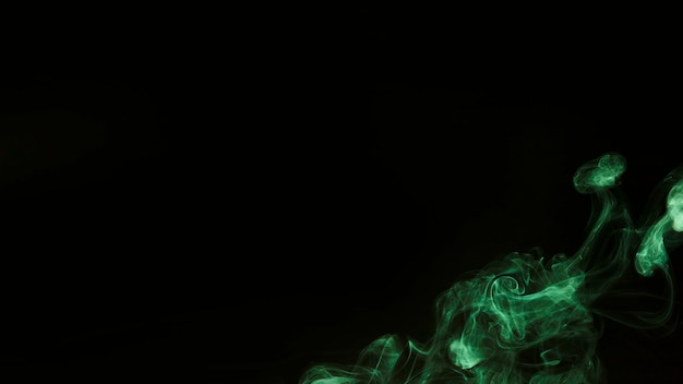 Green wispy smoke on the corner of black background with copy space