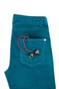 ヘッドフォンで白で隔離される緑の女性のジーンズ。電子機器の現代ファッションのコンセプト。