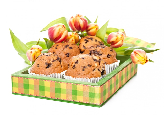 Green wooden tray with muffins and bunch of tulips