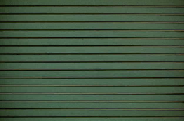 Green wooden wall cladding  texture with repeat pattern of horizontal line in a full frame view.