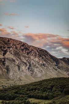 緑の木々の多い地形と曇り空の下の風光明媚な岩、ルーマニアのリメテア村