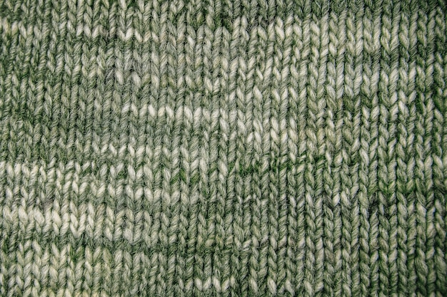 Green wool scarf texture close up. knitted jersey background with a relief pattern. braids in machine knitting pattern