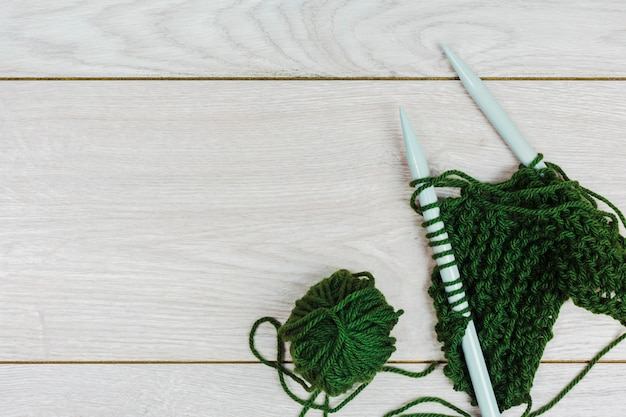 Green yarn crocheting and knitting with needles on wooden backdrop