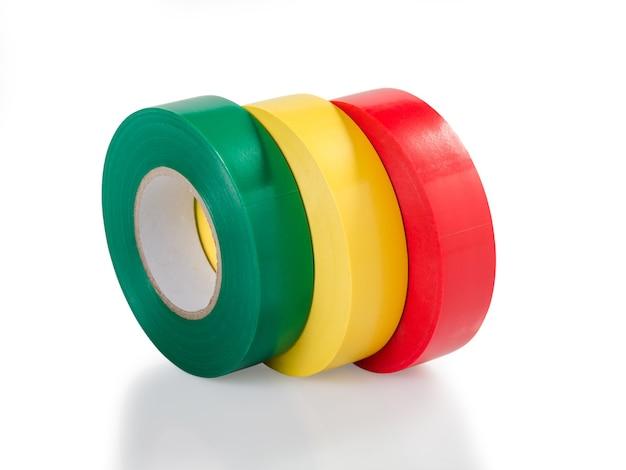 Зеленый, желтый и красный моток изоляционной ленты, изолированные на белой поверхности, обтравочный контур без тени