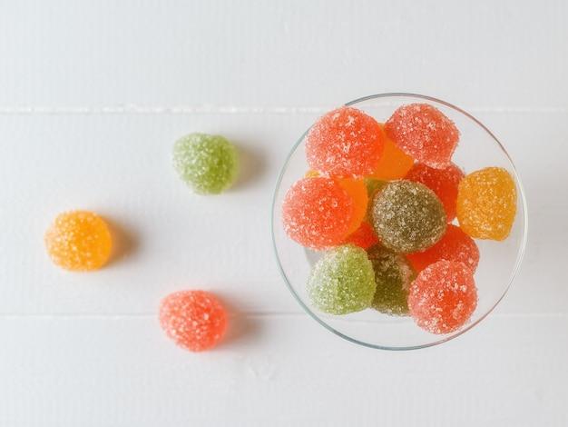 白いテーブルの上のガラスのボウルに緑、黄色、赤のマーマレード。砂糖とゼリーを使った美味しいお菓子。上からの眺め。