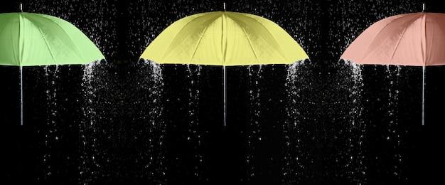 黒の背景と雨滴の下の緑、黄色、赤の傘。ビジネスとファッションのコンセプト。