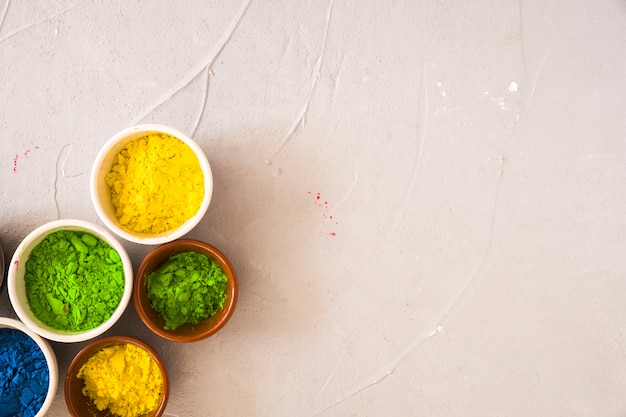 Green; yellow and blue color powder in the bowl on concrete backdrop