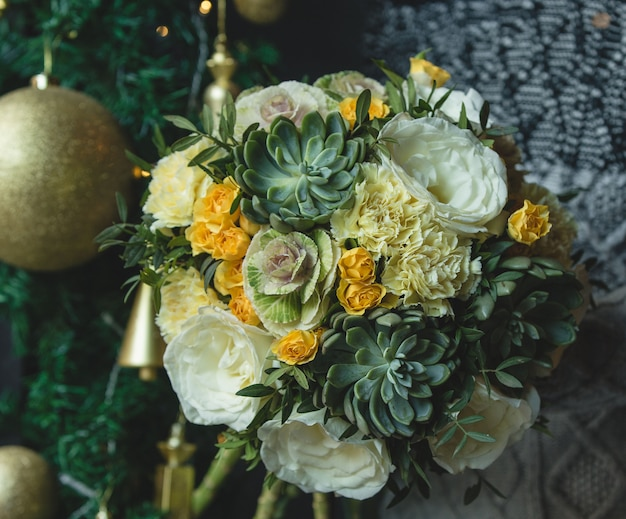 Green yellow bouquet with golden christmas ball.