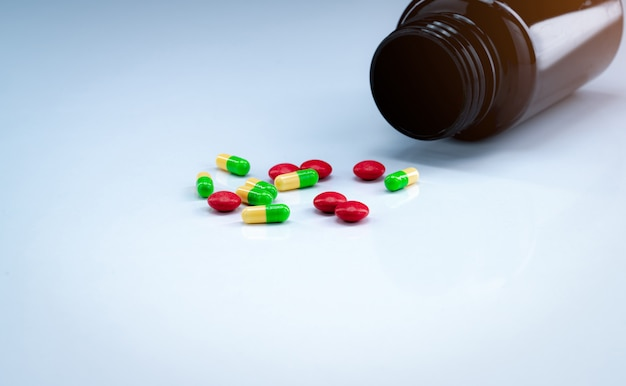 Green and yellow capsules with red tablets pills near brown drug bottle on white background. pharmaceutical industry. painkiller medicine.