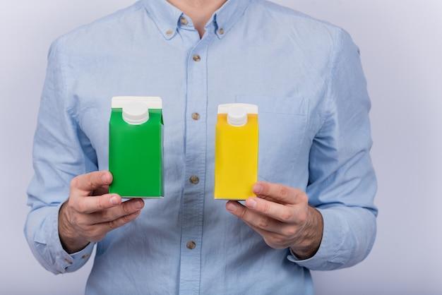 Green and yellow cartones milk or juice in mens hands.