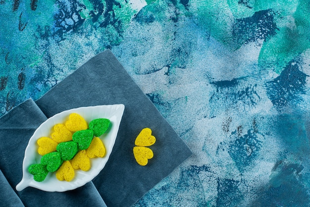 Green and yellow cookies on a plate on a pieces of fabric on the blue surface