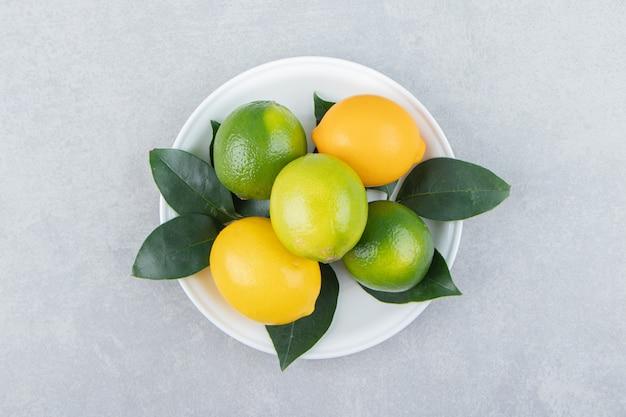 Limoni verdi e gialli sul piatto bianco.