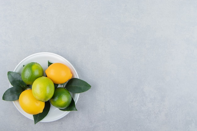 Green and yellow lemons on white plate