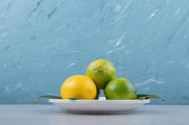 Limoni verdi e gialli sul piatto bianco