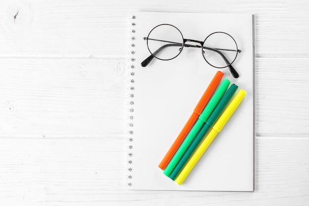 Green and yellow markers, notebook and glasses.