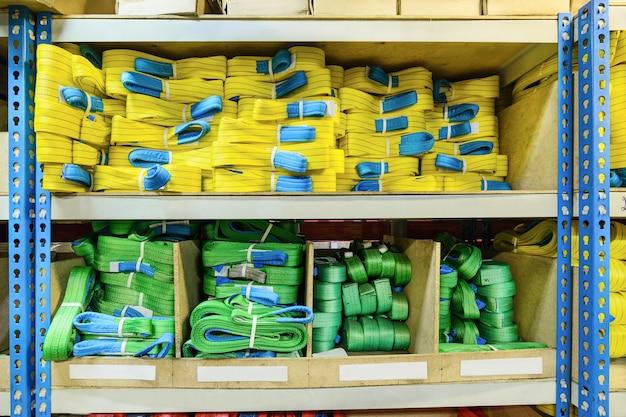말뚝에 쌓인 녹색, 노란색 나일론 소프트 리프팅 슬링. 산업 기업을 위한 완제품 창고