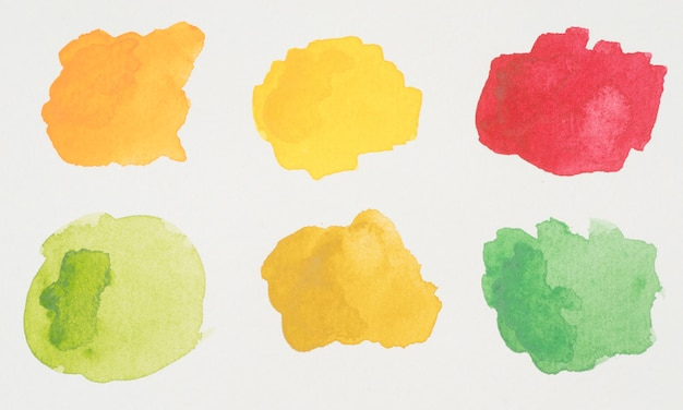 Green, yellow, orange and red blots of paints on white paper