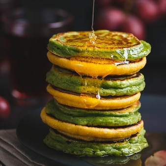Green and yellow pancakes with matcha tea or spinach, corn flour and turmeric, dressed honey