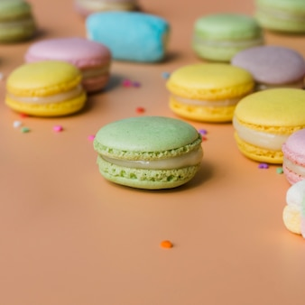 Green; yellow; pink; and blue macaroons on colored background