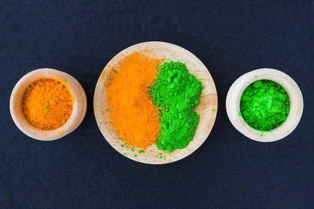 Green and yellow powder in wooden bowl and plate on black backdrop